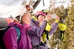 Snowboarders de las mujeres fotografiados en el teléfono Foto de archivo libre de regalías