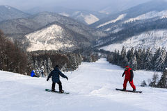 Snowboarders, descent from the mountain. royalty free stock images