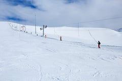 Snowboarders die de berg in Russische polaire skitoevlucht toenemen stock foto's
