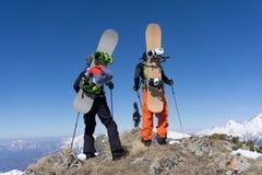 Snowboarders die zich bovenop een berg bevinden Stock Foto