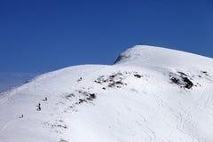 Snowboarders e esquiadores para baixo fora da inclinação da pista no dia do sol Imagem de Stock