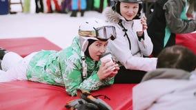 Snowboarders en de skiërs drinken koffie binnen kamperen bij de skitoevlucht Bergen Sport stock video
