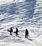 Snowboarders en el sendero en nieve en la mañana del sol Fotografía de archivo