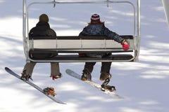 Snowboarders en una elevación de esquí Imagen de archivo