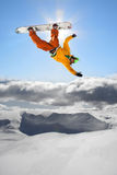 Snowboarders jumping against blue sky Royalty Free Stock Photos