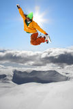 Snowboarders jumping against blue sky Stock Photography