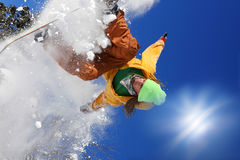 Snowboarders jumping against blue sky Stock Photo