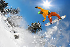 Snowboarders jumping against blue sky Royalty Free Stock Photo