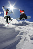 Snowboarders jumping against sun Stock Image