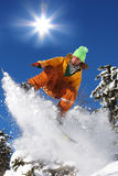 Snowboarders jumping against sun Royalty Free Stock Photos