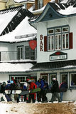 Snowboarders Lining-up to Buy Tickets. Several snowboarders are lining up to buy tickets at the window located under a bar Stock Image