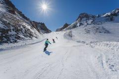 Snowboarders och av berget på en solig dag österrikiska alps Royaltyfri Foto