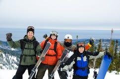 Snowboarders och skiers på berg Arkivfoto