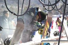 Snowboarders que limpian snowboard Fotografía de archivo libre de regalías