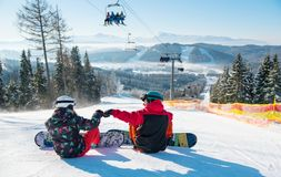 Snowboarders resting on top of ski slope under the lift stock image
