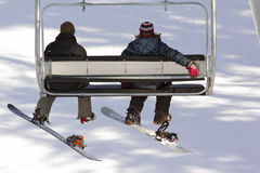 Snowboarders on a ski lift Stock Image