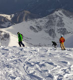 Snowboarders and skier on off-piste slope in sun evening Stock Photos
