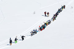 Snowboarders and skiers climb the mountain for freeride. KAMCHATKA PENINSULA, RUSSIA - MARCH 9, 2014: Group of sportsmens - snowboarders and skiers climb the Royalty Free Stock Images