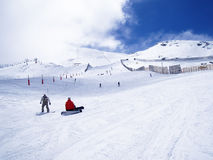 Snowboarders stopped in a snow piste. Two snowboarders taking a rest sitting on the snow, in the middle of a snow piste Stock Photography