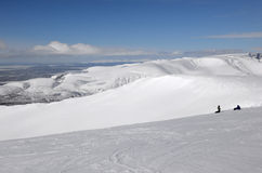 Snowboarders on the top of the winter mountains Stock Images