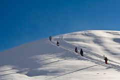 Snowboarders walking up the mountain. In snow Royalty Free Stock Image