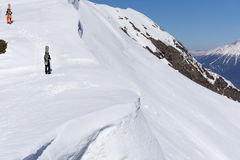 Snowboarders walking uphill for freeride. Extreme sport Stock Image