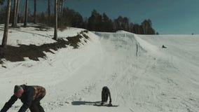 Snowboarders wordt voorbereid met behulp van een snowboardspringplank stock videobeelden