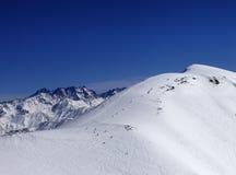 Snowboarders y esquiadores cuesta abajo en de cuesta del piste Foto de archivo
