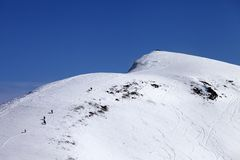 Snowboarders y esquiadores cuesta abajo en de cuesta del piste en el día del sol Imagen de archivo