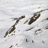 Snowboarders y esquiadores cuesta abajo en cuesta del esquí en el día de invierno del sol Imagenes de archivo