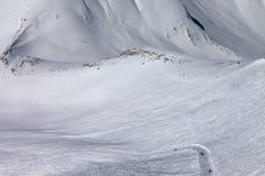 Snowboarders y esquiadores en cuesta y cuesta fuera de pista con el rastro Fotografía de archivo libre de regalías