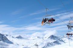 Snowboarders y esquiadores que montan encima de Ski Lift Foto de archivo libre de regalías
