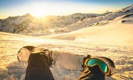Snowboardersammanträde kopplar av på ögonblick på solnedgången skidar in semesterorten Arkivbilder