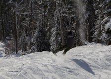 Snowboarderslagberm med stil Lyftande bräde överst, medan släpa svansen på snö arkivfoton