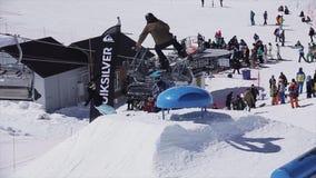 Snowboardersprong hoog over blauwe kicker Zonnige dag Het van brandstof voorzien van de benzinepomp SNEEUW BERGEN stock video