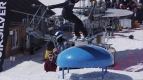 Snowboardersprong over blauwe kicker, aanraking zonnig Het van brandstof voorzien van de benzinepomp SNEEUW BERGEN stock video