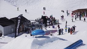 Snowboardersprong over blauwe kicker, greepraad in lucht Zonnige dag Het van brandstof voorzien van de benzinepomp stock videobeelden