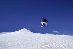Snowboardersprong in terreinpark bij skitoevlucht op de dag van de zonwinter Royalty-vrije Stock Foto's
