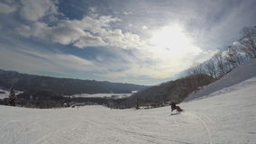 Snowboarding πολύ γρήγορα κάτω από την κλίση, όμορφο χιονώδες τοπίο βουνών στο υπόβαθρο, ακραίος χειμερινός αθλητισμός απόθεμα βίντεο
