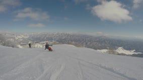 Snowboarding πολύ γρήγορα κάτω από την κλίση, όμορφο χιονώδες τοπίο βουνών στο υπόβαθρο, ακραίος χειμερινός αθλητισμός φιλμ μικρού μήκους