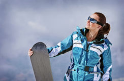 Snowboarding. Sporty girl wearing goggles and holding snowboard in hand, active lifestyle, cloudy background, extreme sport, winter vacation concept Stock Photography