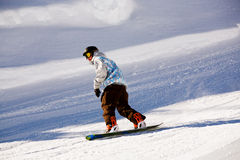 Snowboarding. A snowboarder on the piste. Alps in the winter time Royalty Free Stock Image