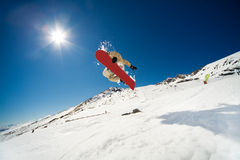 Snowboarding action. Snowboarder jumping through air on blue sky background Royalty Free Stock Photo