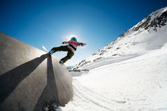 Snowboarding action. Snowboarder on wall ride with blue sky background Royalty Free Stock Photo