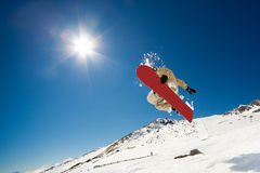 Snowboarding action. Snowboarder jumping through air on blue sky background Stock Photo