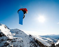 Snowboarding action. Snowboarder jumping through air on blue sky background Royalty Free Stock Images