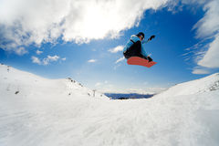 Snowboarding action. Snowboarder jumping through air on blue sky background Royalty Free Stock Photos