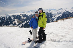 Snowboarding couple in embrace on the top of mountain Stock Photos
