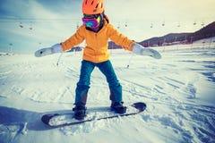 Snowboarding de femme en montagnes Photographie stock
