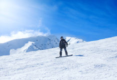 Snowboarding do homem novo na montanha Imagem de Stock